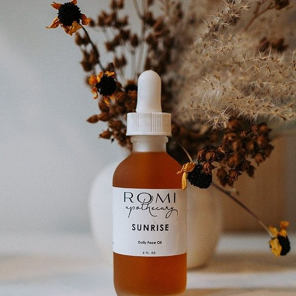 sunshine facial oil by romi apothecary in front of dried florals