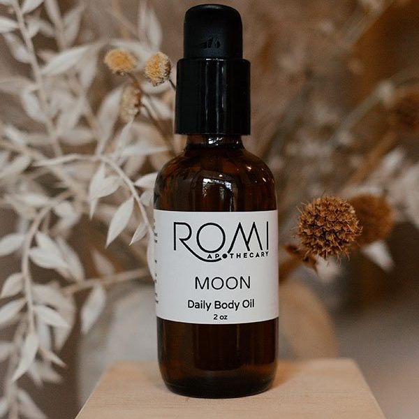 moon body oil by romi apothecary in front of dried florals