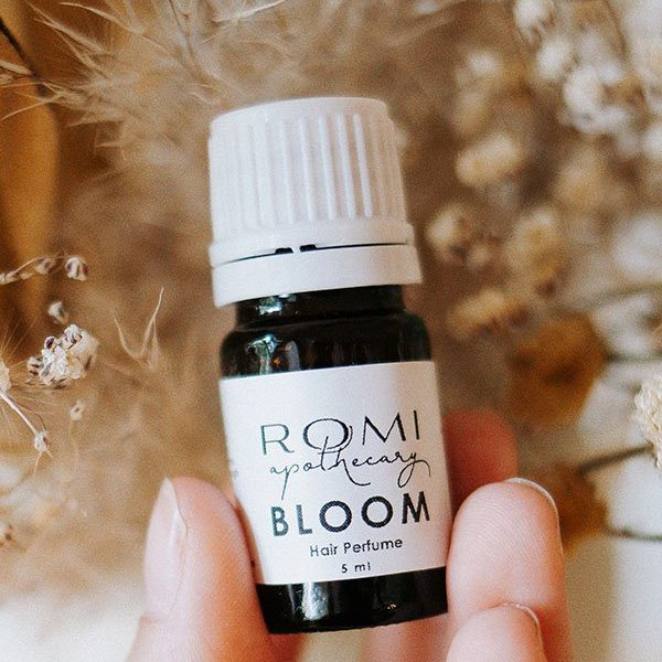 bloom hair perfume by romi apothecary in front of dried florals
