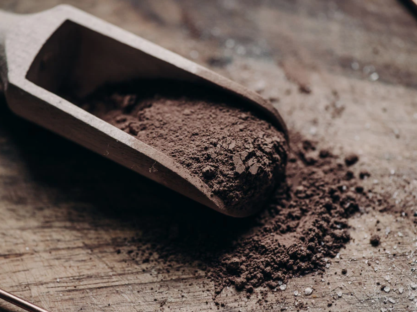 powdered brown cacao in a wooden scoop